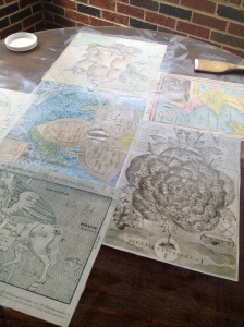Gluing down the maps with Mod Podge.