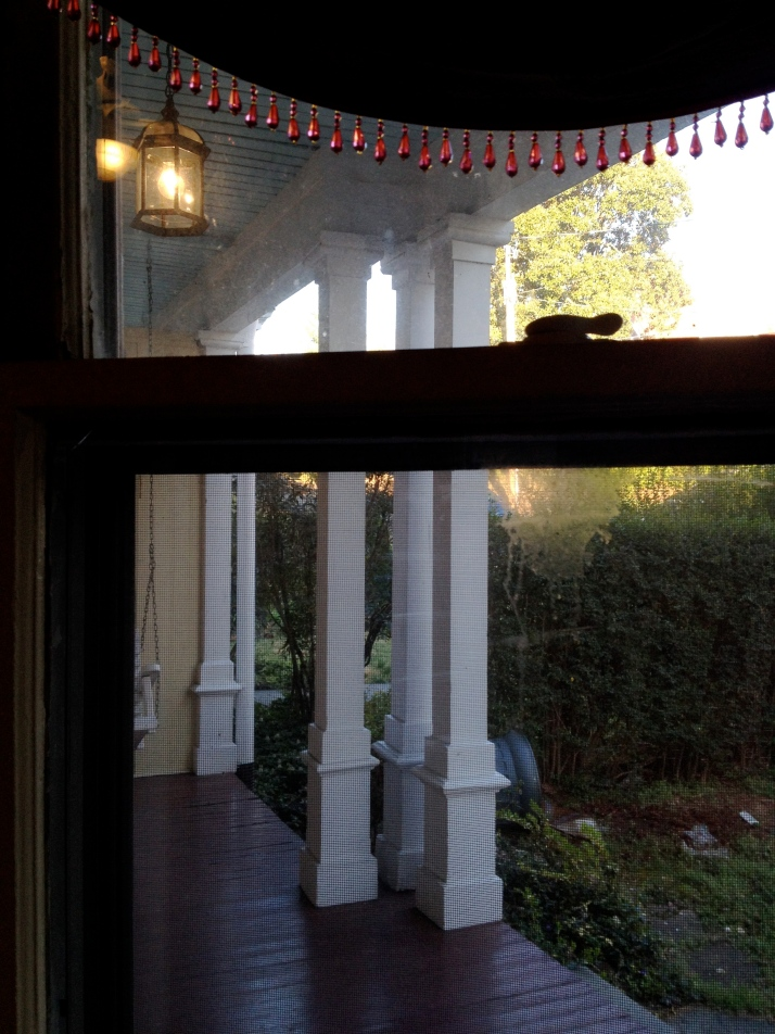 View to the porch through a dirty window.